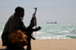 An armed Somali pirate sits along the coastline of Hobyo town in northeastern Somalia on January 7, 2010. (Mohamed Dahir-AFP-Getty)
