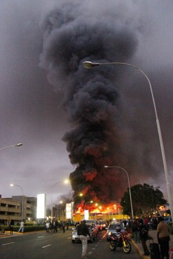 People watch dense black smoke