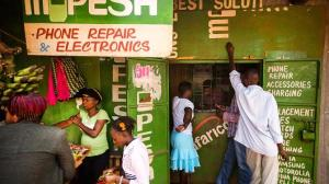 Residents transfer money using the M-Pesa banking service at a store in Nairobi, Kenya