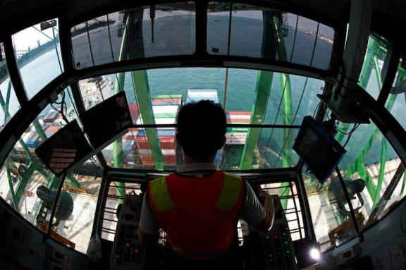 A crane operator unloads containers from a ship at a PSA International port terminal in Singapore