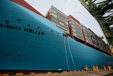 Dock workers tie mooring ropes as the MV Maersk Mc-Kinney Moller berths at a PSA International port terminal in Singapore