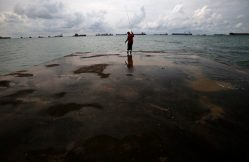 A man fishes on a wharf overlooking container ships anchored at sea, as they wait to berth at port terminals, in Singapore