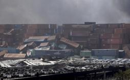 Damaged vehicles and overturned containers are seen near the site of the explosions at the Binhai new district, Tianjin