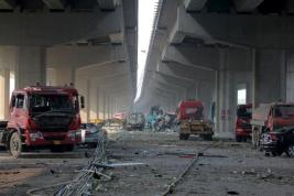 Damaged vehicles are seen under bridges close to the site of the explosions in Tianjin
